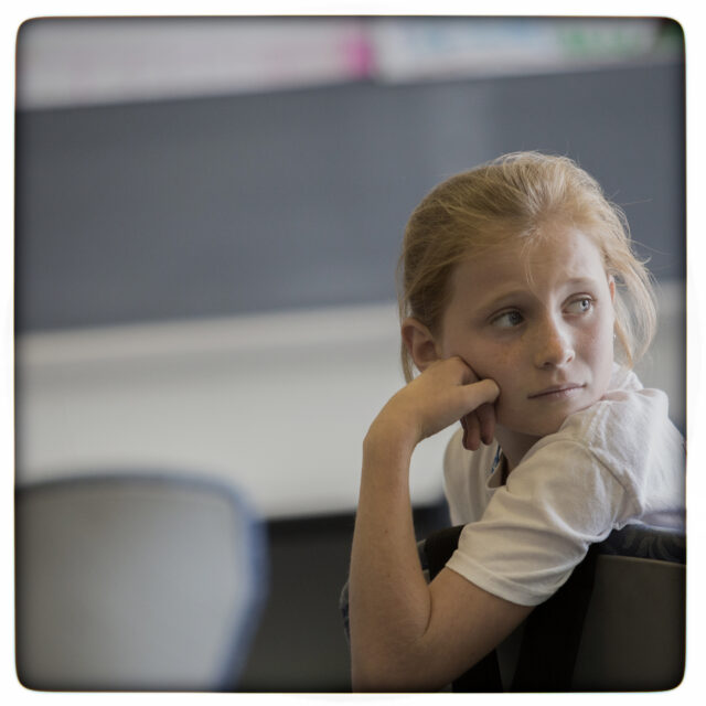 young girl alone in a classroom