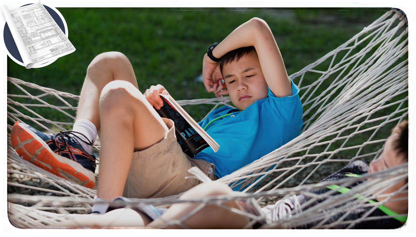 A boy reading a book in a hammock.